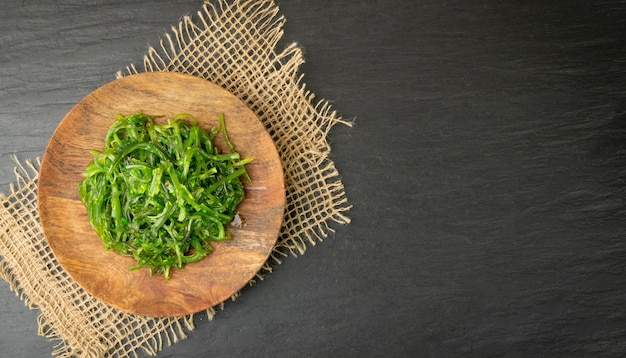 Zielona sałatka z wodorostów chuka na rustykalnym tle widok z góry.
