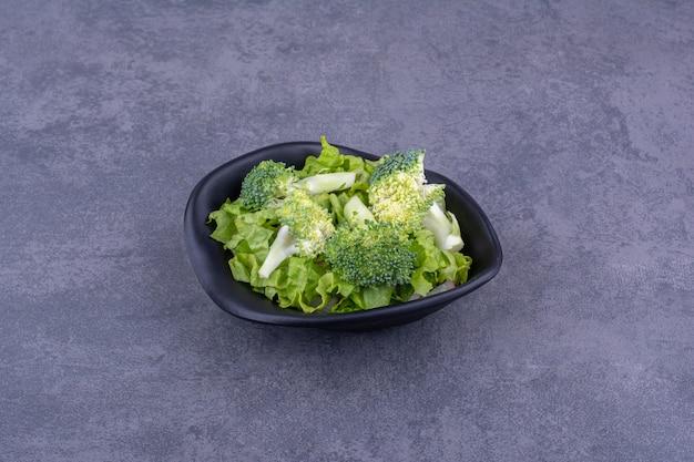 Zielona sałatka z ziołami i przyprawami w ceramicznym talerzu