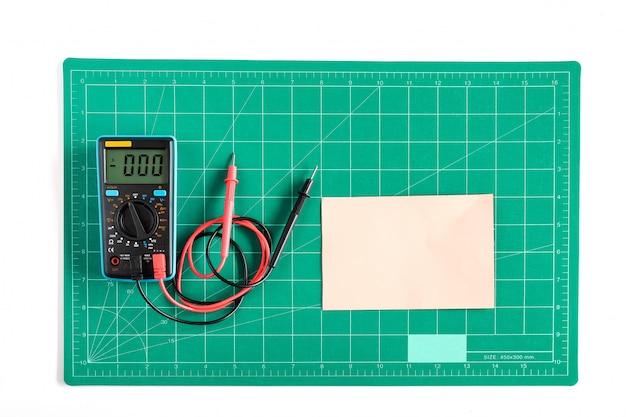 Zielona siatka do cięcia mat lub podkładka z woltomierzem roboczym na tle.