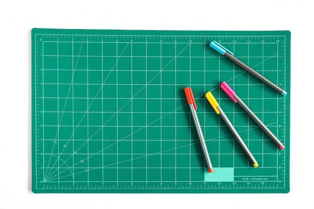 Zielona siatka tnąca matowa lub podkładka z kolorowym piórem na tle.