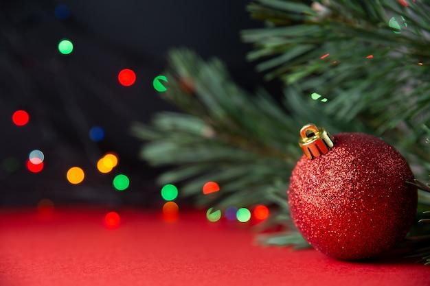 Zielona sosna gałąź i czerwone błyszczące boże narodzenie ball zbliżenie na czerwono-czarnym tle. zimowe tradycyjne wakacje. piękne tło nowy rok lub boże narodzenie, pocztówka. bokeh, selektywne focus, kopia przestrzeń.
