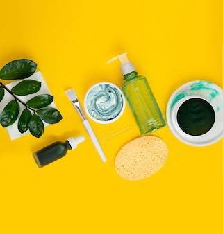 Zielona spirulina diy oczyszczająca maska do twarzy i składniki. widok z góry na płasko: akcesoria do kąpieli, miska