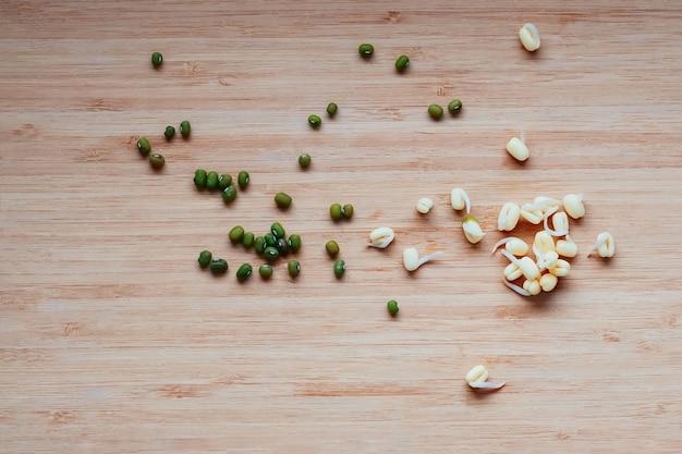 Zielona sucha fasola mung i jej kiełki rozrzucone na kopii z góry na stole