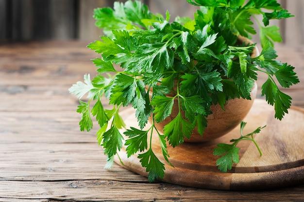 Zielona świeża pietruszka na drewnianym stole, selektywna ostrość