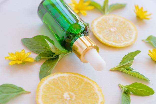 Zielona szklana butelka z olejkiem eterycznym z owoców cytrusowych
