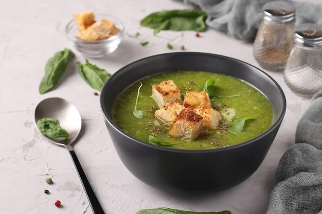 Zielona szpinak puree zupa podawana z grzankami w ciemnej misce na szarym tle betonu, zbliżenie, miejsca na tekst