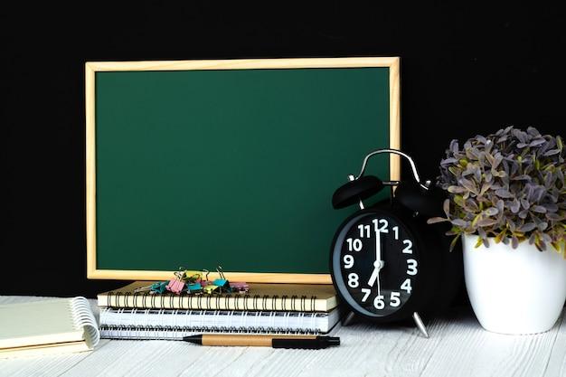 Zielona tablica z kupą zeszytu