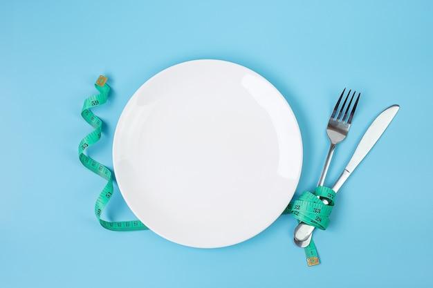 Zielona taśma miernicza owinięta wokół widelca i noża z białym ceramicznym naczyniem na niebieskim tle