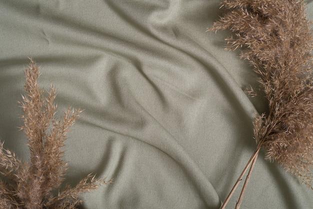 Zielona tkanina w neutralnym kolorze, tkanina lniana w pobliżu wystroju suchej trawy pampasowej