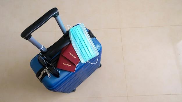 Zielona walizka zebrana na podróż podczas pandemii covid. koncepcyjne wakacje i wyjazdy. rozmiar banera. skopiuj miejsce, selektywna ostrość.