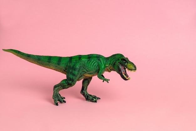 Zielona zabawka dinozaura z otwartymi ustami na pastelowym różu
