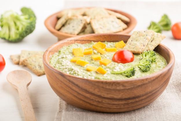 Zielona zupa krem brokułowa z krakersami i serem w drewnianej misce na białej powierzchni drewnianych. widok z boku, selektywne focus.