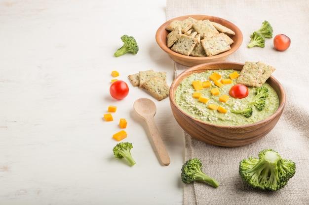 Zielona zupa krem z brokułów z krakersami i serem w drewnianej misce. widok z boku, copyspace.