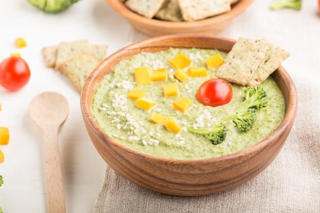 Zielona zupa krem z brokułów z krakersami i serem w drewnianej misce. widok z boku
