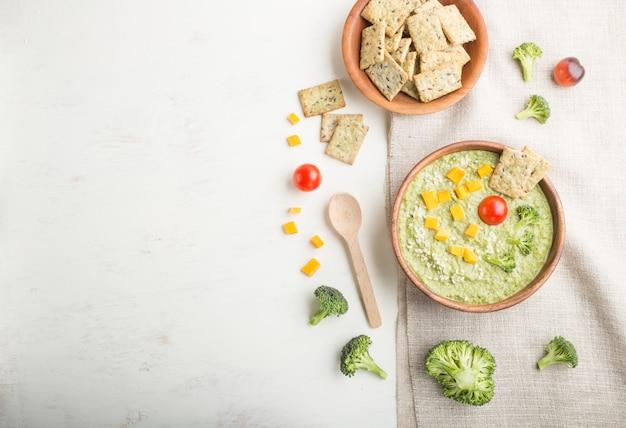 Zielona zupa krem z brokułów z krakersami i serem w drewnianej misce. widok z góry, lato.