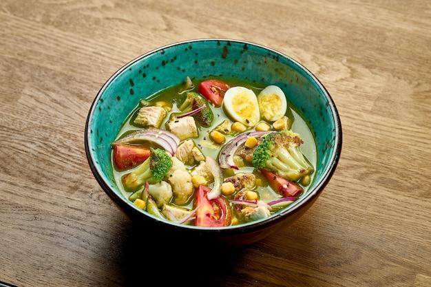 Zielona zupa z brokułami i kalafiorem, cebulą, kurczakiem i jajkiem w misce na drewnianym tle