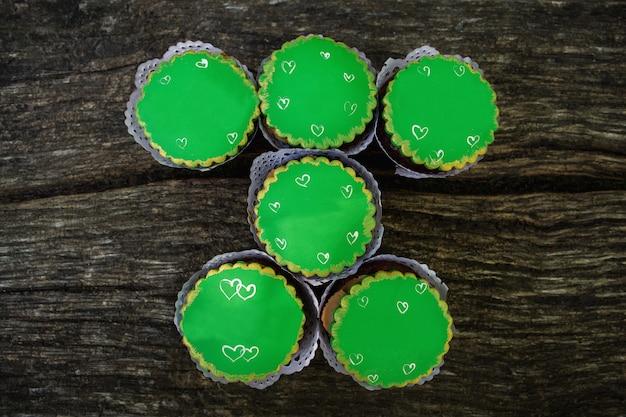 Zielone babeczki na drewnianym tle, cukierki dla świętego patrick dnia