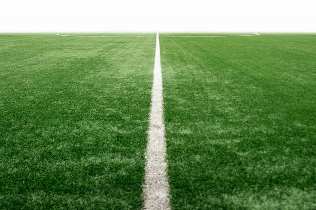 Zielone boisko ze sztuczną trawą, perspektywa boiska do piłki nożnej.