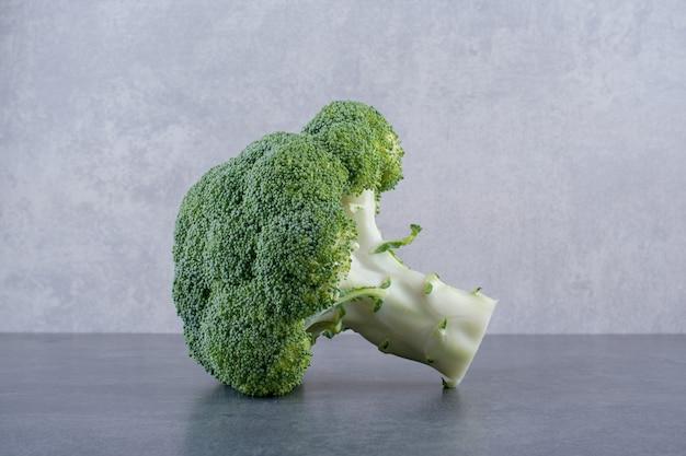 Zielone brokuły na białym tle na betonowym tle.