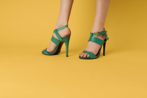 Zielone buty na kobiecych nogach pozowanie zbliżenie żółte tło