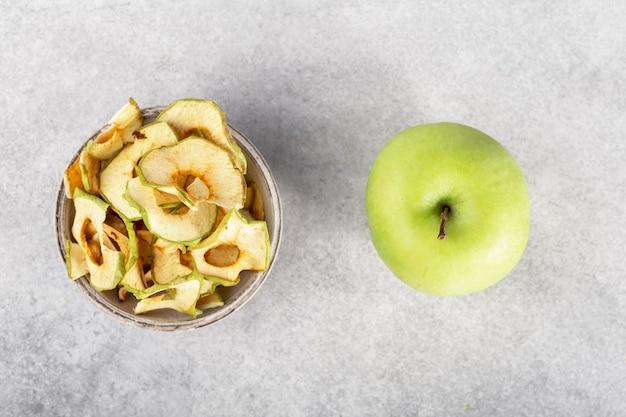 Zielone chipsy jabłkowe w szarej misce na szarym tle