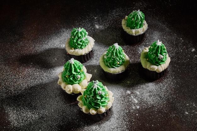 Zielone ciasta z dodatkiem białej śmietany w postaci choinek są w różnej kolejności posypane cukrem pudrem