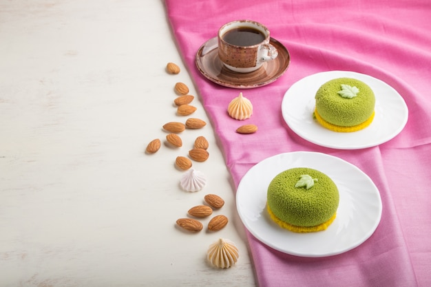 Zielone ciasto mus z kremem pistacjowym i filiżanką kawy. widok z boku, copyspace.