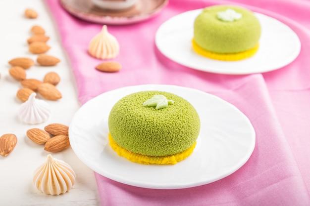 Zielone ciasto mus z kremem pistacjowym i filiżanką kawy. widok z boku