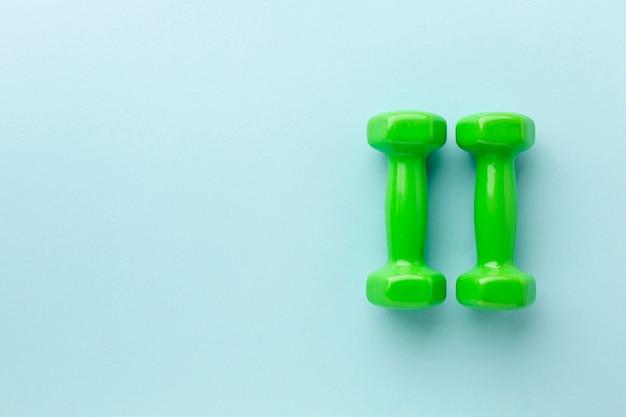 Zielone ciężary na niebieskim tle z miejsca kopiowania