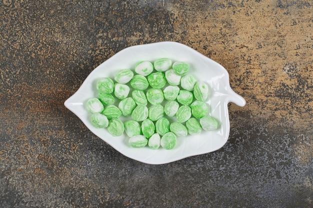 Zielone cukierki mentolowe na talerzu w kształcie liścia.