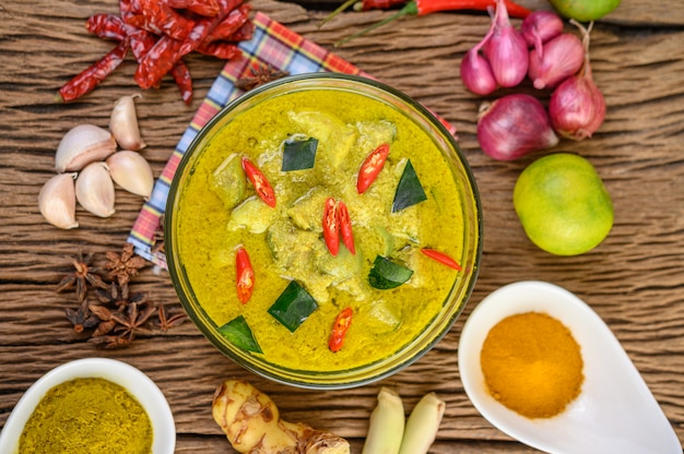 Zielone curry w misce i przyprawy na drewnianym stole.