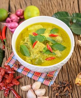 Zielone curry w misce z limonką, czerwoną cebulą, trawą cytrynową, czosnkiem i liśćmi limonki kaffir