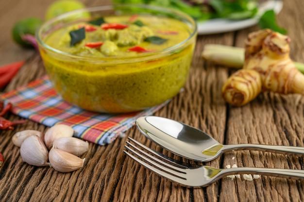 Zielone curry w misce z widelcem i łyżką na drewnianym stole.