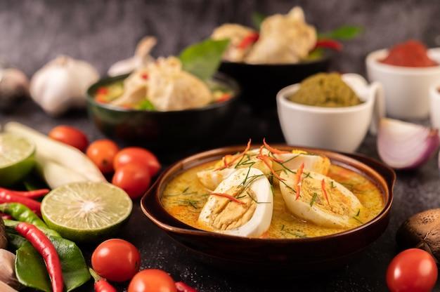 Zielone curry z jajkami w czarnych filiżankach, z cytryną, trawą cytrynową, chili i pomidorami.