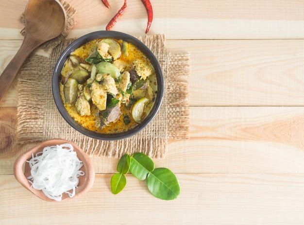 Zielone curry z kurczakiem i makaronem ryżowym na drewnie