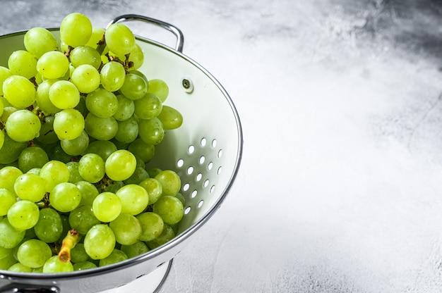Zielone dojrzałe winogrona w durszlaku, owoce jesieni. białe tło.