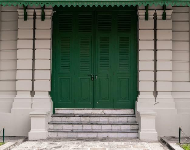 Zielone drzwi z cegły na tle