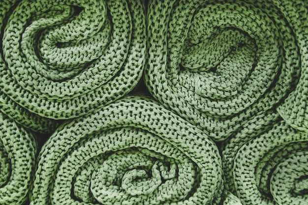 Zielone dzianinowe koce zwinięte w rolki