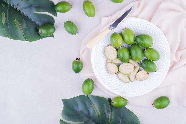 Zielone feijoas w białym talerzu z liśćmi wokół