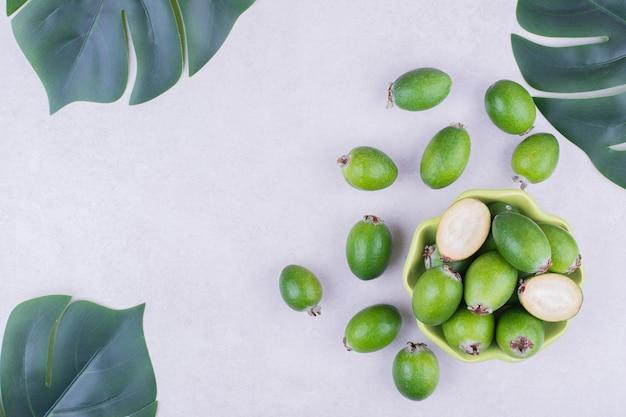 Zielone feijoas w zielonej filiżance z liśćmi wokół