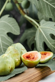 Zielone figi na desce otoczonej liśćmi, selektywne focus.