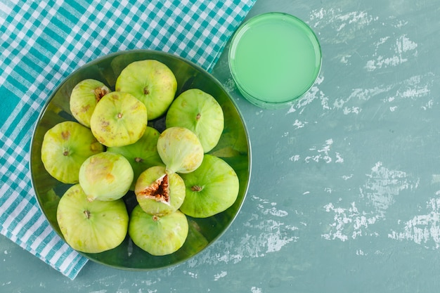 Zielone figi na talerzu z napojem leżą płasko na tynku i szmatce piknikowej