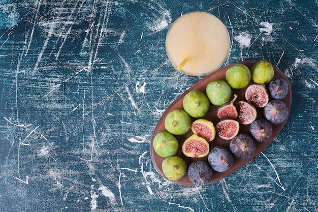 Zielone figi przy filiżance napoju na niebiesko.
