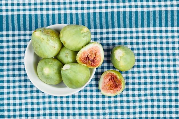 Zielone figi w białej misce i na drewnianym stole z niebieskim obrusem. wysokiej jakości zdjęcie