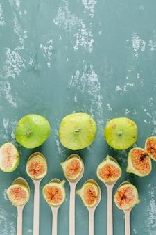 Zielone figi w drewnianych łyżkach na tynku. widok z góry.
