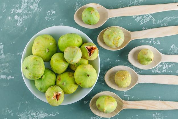 Zielone figi w talerzu i drewniane łyżki na ścianie gipsowej, układane na płasko.