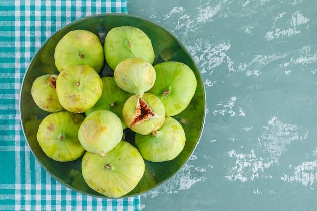 Zielone figi w talerzu na gipsie i szmatki piknikowej. leżał płasko.
