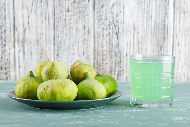 Zielone figi w talerzu z widokiem z boku napoju na tynku i drewnianym stole