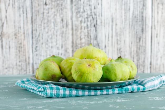 Zielone figi w talerzu z widokiem z boku tkaniny piknikowej na tynku i drewnianym stole