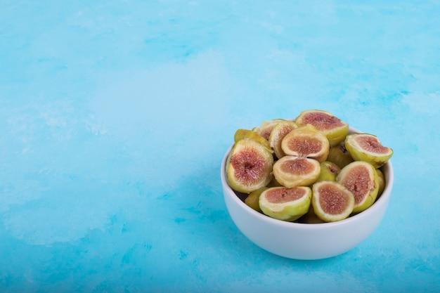 Zielone figi z czerwonymi nasionami w białej ceramicznej misce, kąt widzenia.